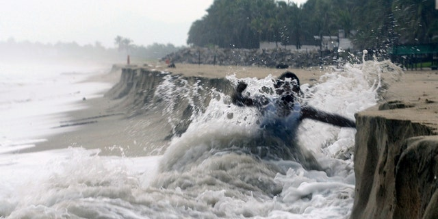 Sept. 14, 2017: A man fights against waves caused by approaching Hurricane Max that took away part of the beach in Pie de La Cuesta, on the outskirts of Acapulco, Mexico