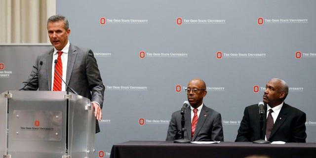 Urban Meyer addresses the media Wednesday night as Ohio State President Dr. Michael Drake, center, and athletic director Gene Smith listen.