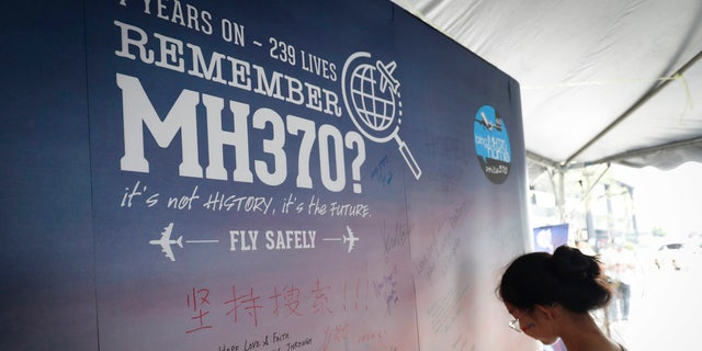 In this March 3, 2018, file photo, a girl writes a condolence message during the Day of Remembrance for MH370 event in Kuala Lumpur, Malaysia.
