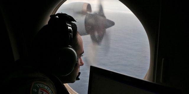 In this March 22, 2014, file photo, flight officer Rayan Gharazeddine scans the water in the southern Indian Ocean off Australia from a Royal Australian Air Force AP-3C Orion during a search for the missing Malaysia Airlines Flight MH370.