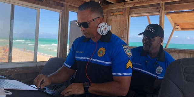 Officers keep watch - and the tunes flowing - from a refurbished lifeguard stand in Miami Beach.