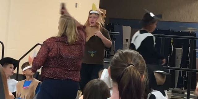 Caleb Riddle, 6, is shown on stage the moment a teacher tries to grab the microphone from its stand. The viral video of the incident has prompted backlash against the teacher.
