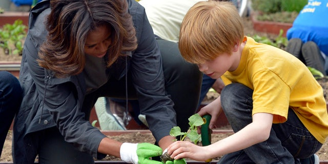 April 2, 2014: First lady Michelle Obama and Bancroft Elementary School student Silas Stutz plant broccoli in the White House Kitchen Garden in Washington.