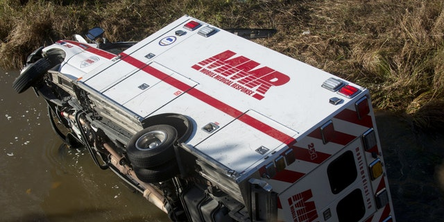 An Mobile Medical Response ambulance rests in Misteguay Creek Monday, Oct. 16, 2017, after colliding with car on a bridge in Maple Grove Township, Mich.