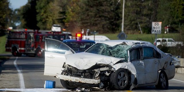 A car rests on a bridge Monday, Oct. 16, 2017, after colliding with a Mobile Medical Response ambulance in Maple Grove Township, Mich.