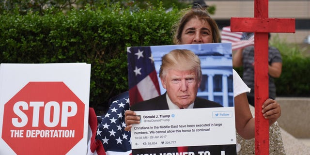Amal Hana, of Warren, Mich., holds a photo of Donald Trump on Friday, June 16, 2017, outside the Patrick V. McNamara Federal Building during a protest in Detroit. Hana said a family member, whom she did not wish to name further, who has lived in the U.S. for 25 years was detained during the recent Immigration and Customs Enforcement raids of primarily Chaldean immigrants and is facing deportation. Hana joined hundreds others to protest the recent ICE raids in which more than 100 Iraqi nationals in Metro Detroit were detained. (Tanya Moutzalias/MLive.com via AP)