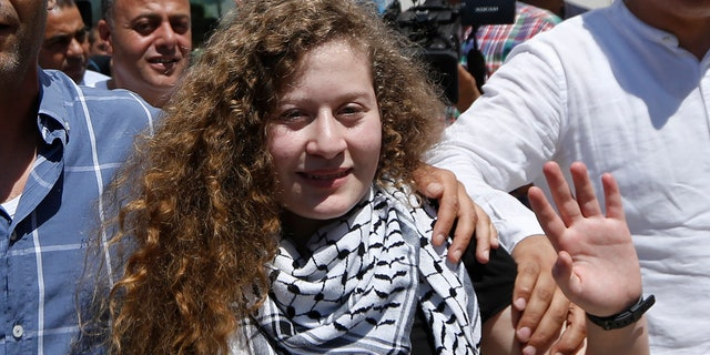 Ahed Tamimi waves after she visited the tomb of former Palestinian leader Yasser Arafat in the West Bank city of Ramallah.