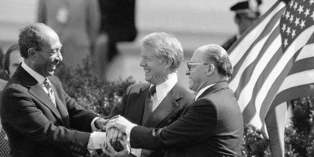 Egyptian President Anwar Sadat, left, President Jimmy Carter, center, and Israeli Prime Minister Menachem Begin clasp hands to symbolize their mutual pleasure upon signing Middle East Peace Treaty at the White House in Washington, March 27, 1979. (AP Photo)