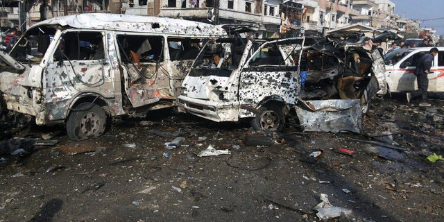 Syrian citizens gather at the scene where two blasts exploded in the pro-government neighborhood of Zahraa, in Homs province, Syria.
