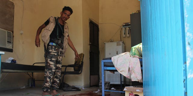 A Yemeni man inspects an elderly care home that was attacked Friday by unidentified gunmen.