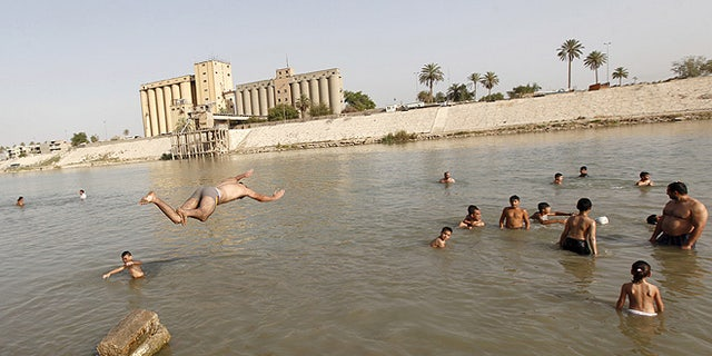 """Residents dive into the Tigris river to take a swim and cool off in northern Baghdad's Adhamiya district. A searing heat wave through Iraq prompted the government to declare a four-day """"Heat Holiday."""" (REUTERS/Ahmed Saad)"""