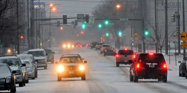Traffic moves down a snow covered street in Bismarck, N.D., Monday, March 5, 2018, as snow falls.