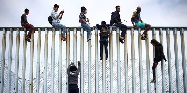 Members of a caravan of migrants from Central America climb up the border fence between Mexico and the U.S., as a part of a demonstration prior to preparations for an asylum request in the U.S., in Tijuana, Mexico April 29, 2018.