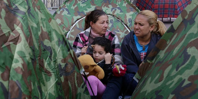 Dozens of Cubans are camped out in front of Mexico's embassy appealing for help in reaching the United States, in Quito, Ecuador, Tuesday, June 21, 2016. They apparently seek something like an international operation earlier this year that lifted thousands of Cubans from Costa Rica to Mexico, so that they could reach the U.S. Unlike any other nationality, Cubans are essentially granted residence if they reach U.S. territory. (AP Photo/Dolores Ochoa)