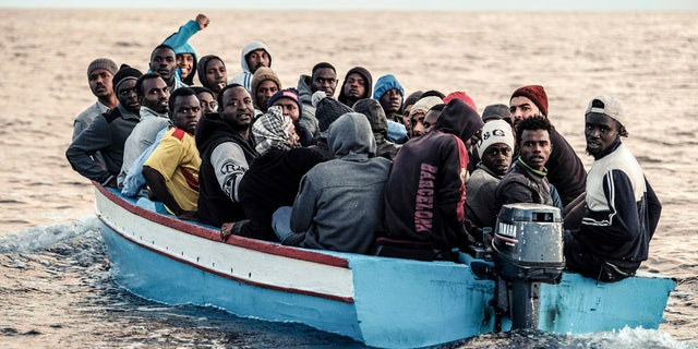 Migrants on a small wooden boat wait to be rescued by the German non-profit organization Sea Watch.