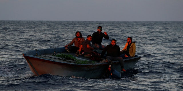 (L-R) Libyan migrants Alaa, Rami, Hamza, Mohammed, and Rafat on a wooden boat await rescue by the migrant search and rescue vessel MV Seefuchs of the German NGO Sea-Eye in the search and rescue zone some fifty nautical miles north of the Tunisian-Libyan land border, September 30, 2017.