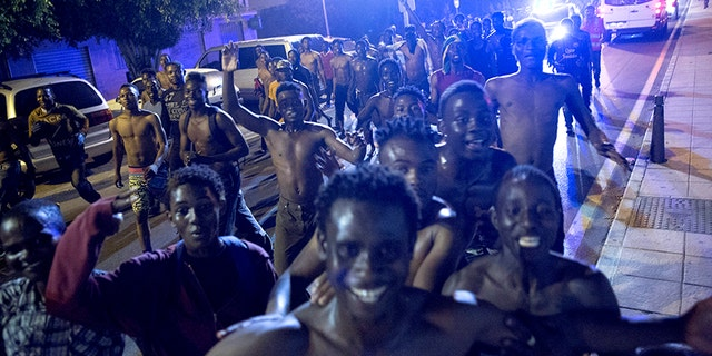 African migrants react after crossing the border from Morocco to Spain's North African enclave of Ceuta.