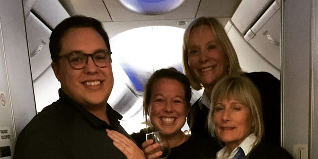 The happy couple with the flight crew after Sam popped the question.