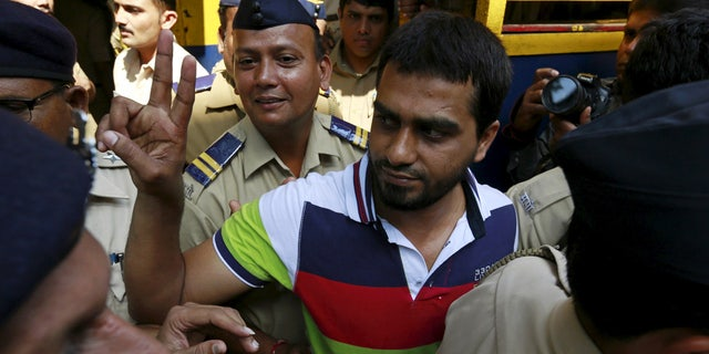 One of the 12 men, convicted of planning several blasts on crowded commuter trains in the financial capital of Mumbai in 2006, gestures as he is escorted by police to a court in Mumbai, India, September 30, 2015.