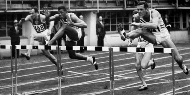 July 26, 1952: This file photo shows Milt Campbell, center, of Plainfield, N.J. getting set to clear the final hurdle to make him the winner in the fifth heat of the 110-meter hurdles event in the Olympic decathlon at Helsinki, Finland.
