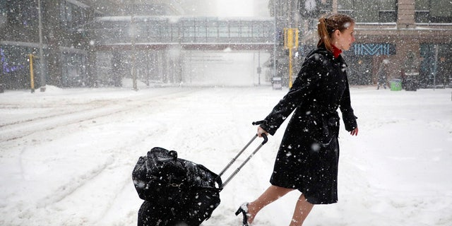 A Delta Airlines flight attendant negotiates the snowy streets of Minneapolis, Minn. Saturday afternoon.