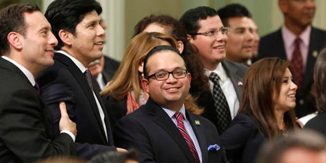FILE - In this Sept. 12, 2013 file photo, Assemblyman Luis Alejo, D-Watsonville, center, smiles as he and other members of the Latino Caucus watch the votes being posted for Alejo's immigrant driver's license bill that was approved by the Assembly in Sacramento, Calif. California has about two dozen Latino lawmakers, yet that's just half their proportion of the state' population. Minorities remain significantly underrepresented in most state Legislatures and Congress despite comprising a growing share of the U.S. population, according to an analysis of demographic data by the Associated Press. (AP Photo/Rich Pedroncelli, File)