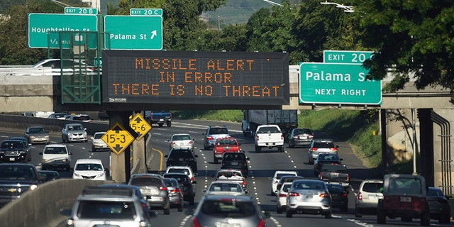 """In this Saturday, Jan. 13, 2018 photo provided by Civil Beat, cars drive past a highway sign that says """"MISSILE ALERT ERROR THERE IS NO THREAT"""" on the H-1 Freeway in Honolulu."""