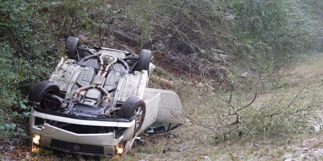 In this image, a car sits upside down on the side of the road after the vehicle flipped in front of the Mississippi State team bus in Mississippi, as the players were heading to LSU for an NCAA college basketball game.