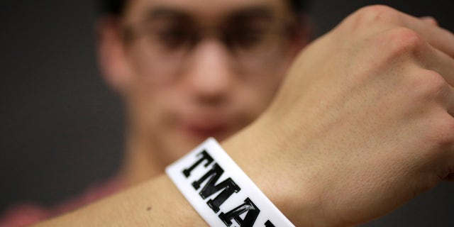 """In this Monday, Feb. 1, 2016 photo, Massachusetts Institute of Technology student Andy Trattner, of Portland, Ore., displays a wrist band that features the acronym TMAYD for """"Tell Me About Your Day,"""" a campaign to encourage students to talk to one another in an effort to defuse to the stress of campus life before it leads to a crisis. There were several campus suicides last year. MIT officials recently set aside thousands of dollars for grants to help support campus projects dealing with mental health. (AP Photo/Steven Senne)"""
