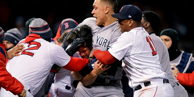 New York Yankees right fielder Aaron Judge puts Boston Red Sox relief pitcher Joe Kelly in a headlock after Kelly hit Yankees' Tyler Austin with a pitch during the seventh inning of a baseball game at Fenway Park in Boston.