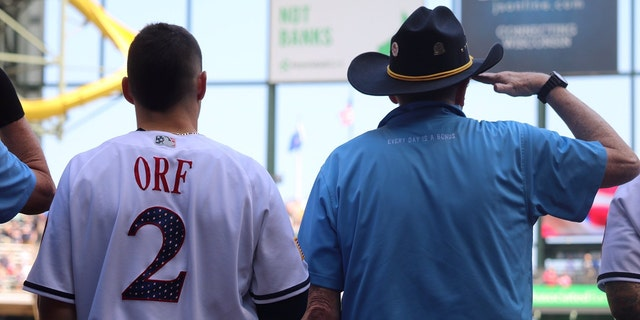A veteran stands next to Brewers player Nate Orf.
