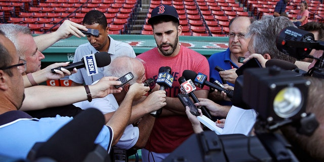 Boston Red Sox's J.D. Martinez is surrounded by reporters while discussing social media postings he made prior to joining the team prior to a baseball game at Fenway Park.