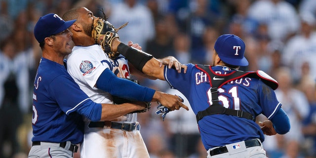Texas Rangers starting pitcher Cole Hamels, left, restrains Los Angeles Dodgers' Matt Kemp as Kemp scuffles with Rangers catcher Robinson Chirinos during the third inning of a baseball game.