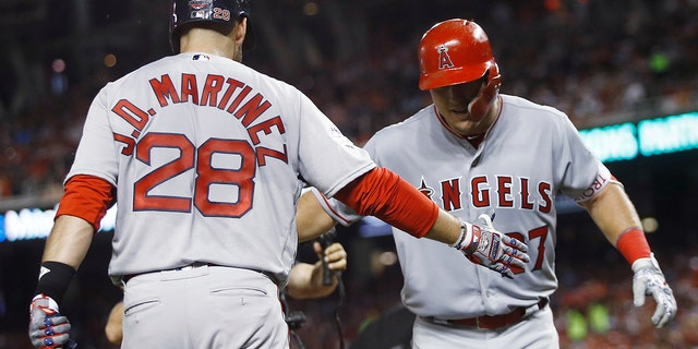 Los Angeles Angels outfielder Mike Trout, right, is welcomed at the dugout by All-Star Game teammate J.D. Martinez after belting a solo home run during the third inning.