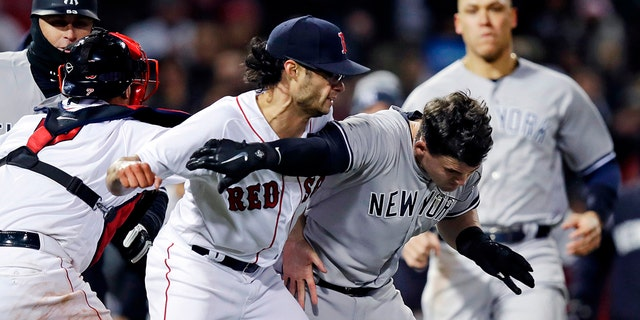 New York Yankees' Tyler Austin, right, scuffles with Boston Red Sox relief pitcher Joe Kelly, after being hit by a pitch during the seventh inning of a baseball game at Fenway Park in Boston.