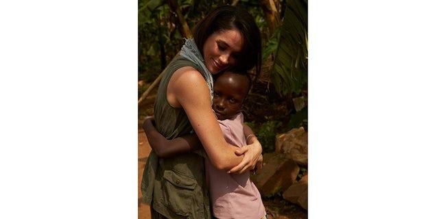 Meghan Markle hugging a child.