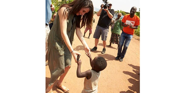 Meghan Markle dancing with a child from the community.