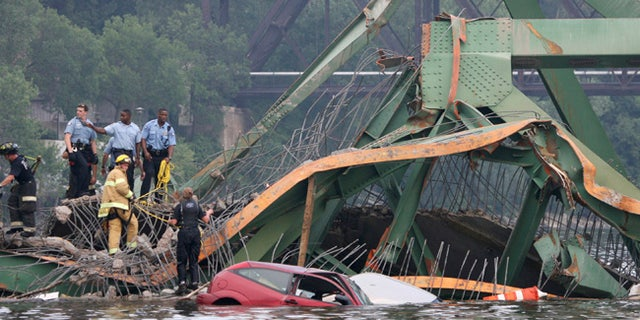 Emergency personnel work at the scene where the Interstate 35W bridge collapses over the Mississippi River in Minneapolis.