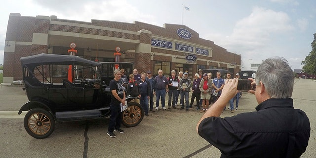 In this Aug. 31, 2017 photo, Gilmore Car Museum official Jay Follis takes a photo of students who completed the museum's Model T driving class in Hickory Corners, Mich. More than 500 people this year took the one-day, four-hour course offered by the museum near Kalamazoo. (AP Photo/Mike Householder)