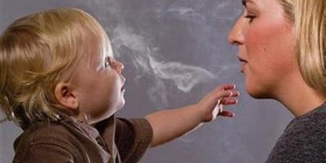 """This handout image, released on November 10, 2010 depicts a mother blowing cigarette smoke in a child's face in one of the Federal Drug Administration's proposed new """"graphic health warnings."""""""