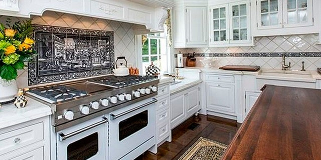 Kitchen highlights include a ten burner stove, sprawling island, and plenty of cabinet space.