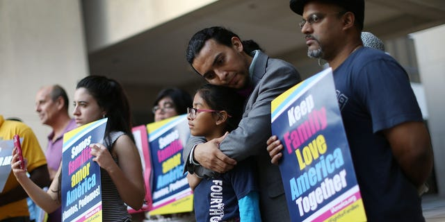 MIAMI, FL - APRIL 18:  Danilo Balladares holds onto Dely Balladares as they join others during a vigil to support President Barack Obama's immigration executive action on April 18, 2016 in Miami, Florida. The U.S. Supreme Court started to hear oral argument on President Obama's deferred action initiatives, DAPA and expanded DACA.  (Photo by Joe Raedle/Getty Images)