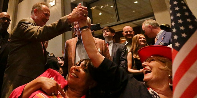 Former Alabama Chief Justice and U.S. Senate candidate Roy Moore, greets supporter Patricia Jones, right, before his election party, Tuesday, Sept. 26, 2017, in Montgomery, Ala.