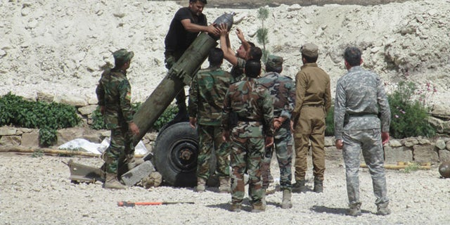 When it was ready to fire, the Peshmerga fighters crouched behind sandbags in case the mortar blew up.