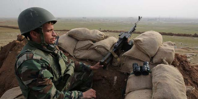 Jan. 27, 2015: A Kurdish Peshmerga soldier stands guard, overlooking the road between Mosul and Tal afar at the frontline of Eski Mosul. (AP)