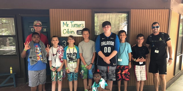 A group of campers and counselors staying in Mr. Turner's honorary cabin pose for a picture, thanking the WWII veteran.
