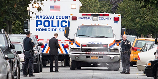 Nassau and Hempstead police investigate the scene of a triple homicide in Hempstead, N.Y., Saturday.