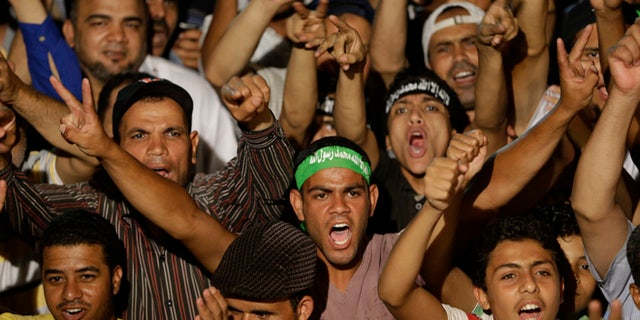 July 10, 2013: Supporters of ousted Egypt's President Mohammed Morsi shout slogans during a demonstration after the Iftar prayer, evening meal when Muslims break their fast during the Islamic month of Ramadan, in Nasr City, Cairo, Egypt.