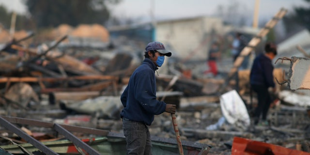A man walks through the scorched ground of the open-air San Pablito fireworks market, in Tultepec, Mexico, Dec. 20, 2016.
