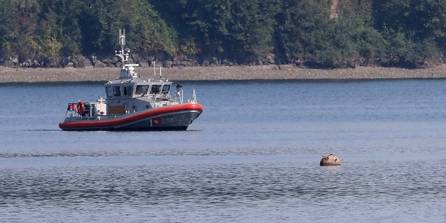 """A U.S. Coast Guard boat keeps watch over a """"reported unexploded ordnance"""" drifting in the water between Brownsville Marina and Bainbridge Island, off Brownsville, Wash., Tuesday, Aug. 28, 2018."""